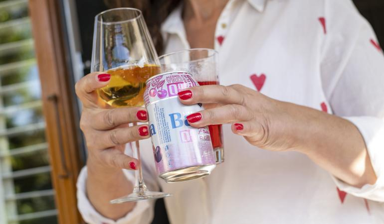 Vrouw met glas wijn en alcoholvrij blikje bier in handen