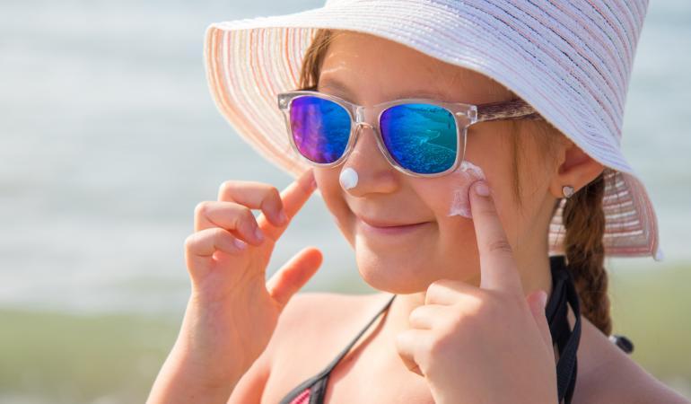 Jong meisje met zonnebrandcreme op gezicht