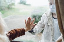 Handen tegen het raam van oudere (binnen) en kind (buiten)