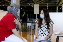 Vrouw krijgt uitleg COVID-19 vaccinatie